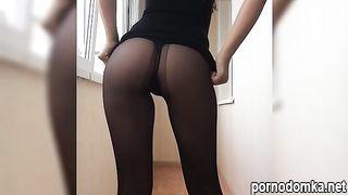 Девушка с очень стройными ножками в черных колготках задирает юбку