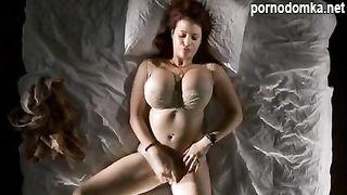 Рыжая девчушка с шикарными сиськами мастурбирует на кровати