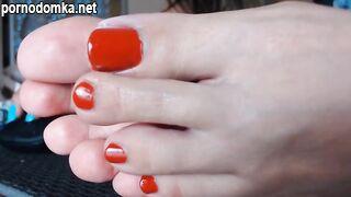 Девушка показывает ноги и красный педикюр на ногтях на камеру