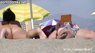Подглядывание за бритой пиздой пышной нудистки на пляже